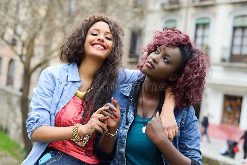 Duas meninas bonitas em mulheres urbanas do backgrund, as pretas e as misturadas fotografia de stock royalty free