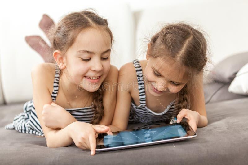 Retrato de duas meninas de sorriso que encontram-se no sofá e que usam a tabuleta foto de stock