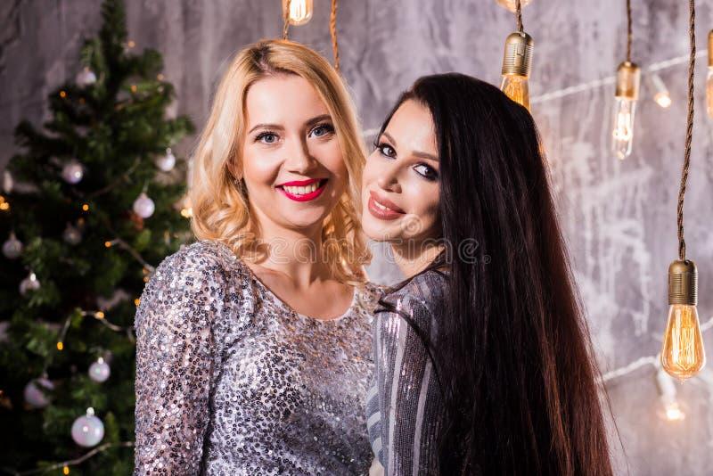 Retrato de duas mulheres bonitas bonitas nos vestidos sparkly que abraçam e que olham a câmera isolada sobre a árvore de Natal imagens de stock