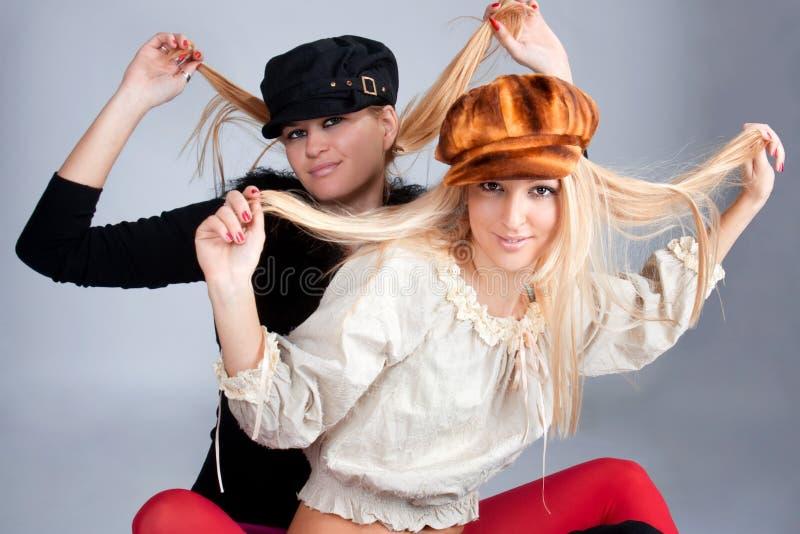 Retrato de duas mulheres bonitas que desgastam tampões imagem de stock