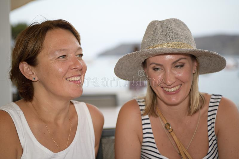 Retrato de duas mulheres felizes que sentam-se ao lado do mar e do sorriso imagens de stock royalty free
