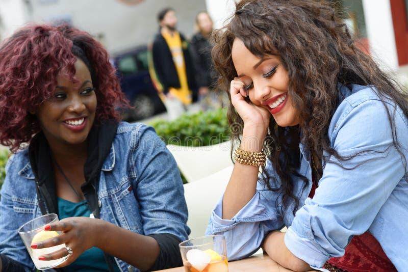 Retrato de duas mulheres que tomam uma bebida em uma barra Fundo urbano foto de stock