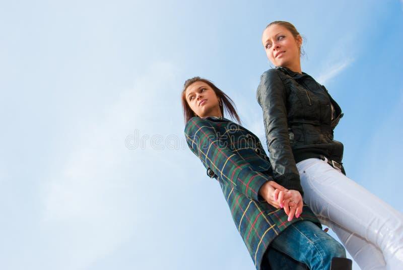 Retrato de duas raparigas sobre o céu imagens de stock