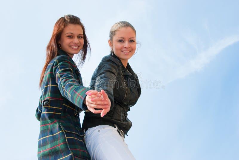 Retrato de duas raparigas sobre o céu fotografia de stock royalty free