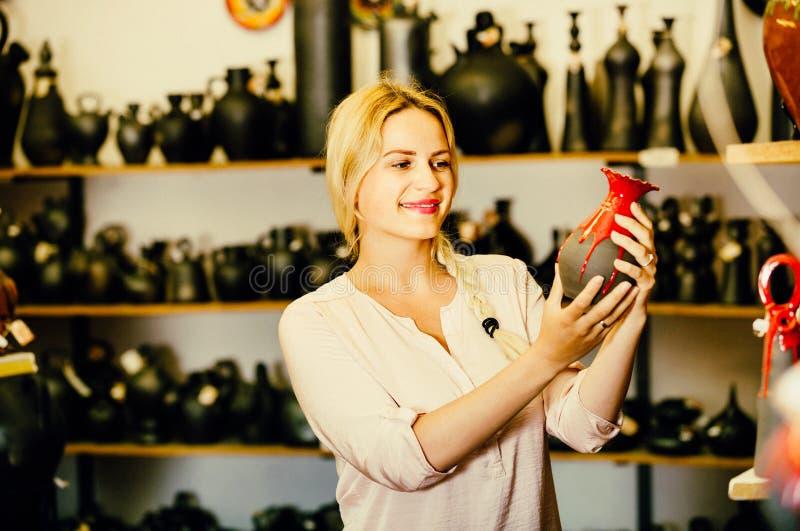 Retrato de elegir alegre de la mujer esmaltado con el ut de cerámica del color rojo fotos de archivo
