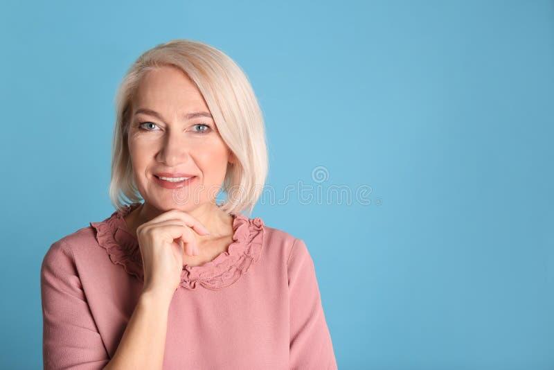 Retrato de encantar la mujer madura con la piel hermosa sana de la cara y el maquillaje natural en fondo azul imágenes de archivo libres de regalías