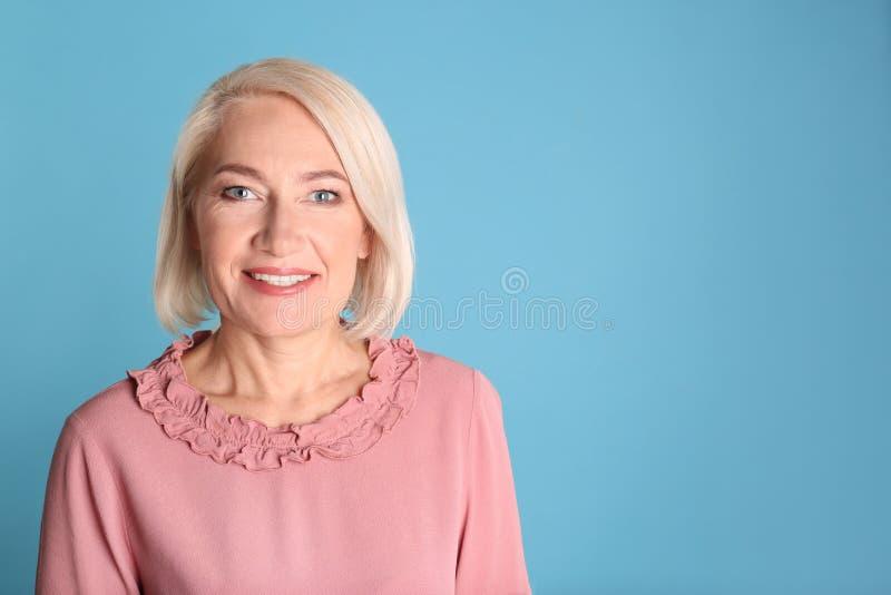 Retrato de encantar la mujer madura con la piel hermosa sana de la cara y el maquillaje natural en fondo azul imagen de archivo libre de regalías