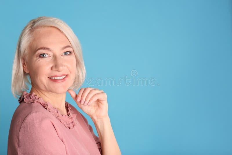 Retrato de encantar la mujer madura con la piel hermosa sana de la cara y el maquillaje natural en fondo azul imagenes de archivo