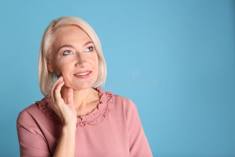 Retrato de encantar la mujer madura con la piel hermosa sana de la cara y el maquillaje natural en fondo azul fotografía de archivo