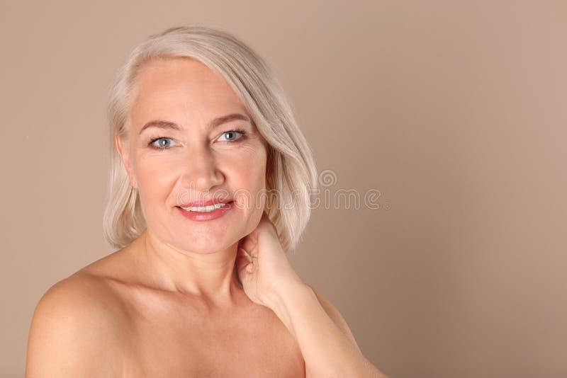 Retrato de encantar la mujer madura con la piel hermosa sana de la cara y el maquillaje natural en fondo beige imagen de archivo