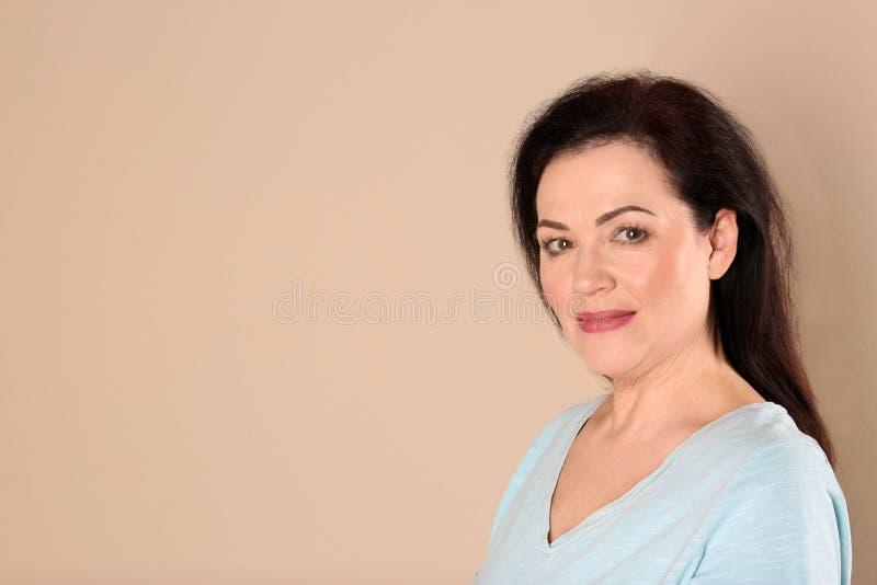 Retrato de encantar la mujer madura con la piel hermosa sana de la cara y el maquillaje natural en fondo beige imagen de archivo libre de regalías