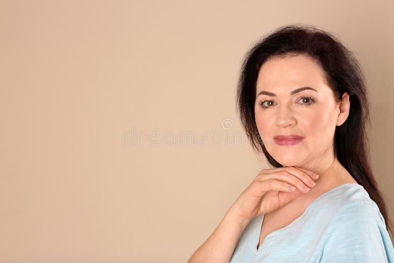 Retrato de encantar la mujer madura con la piel hermosa sana de la cara y el maquillaje natural en fondo beige imágenes de archivo libres de regalías