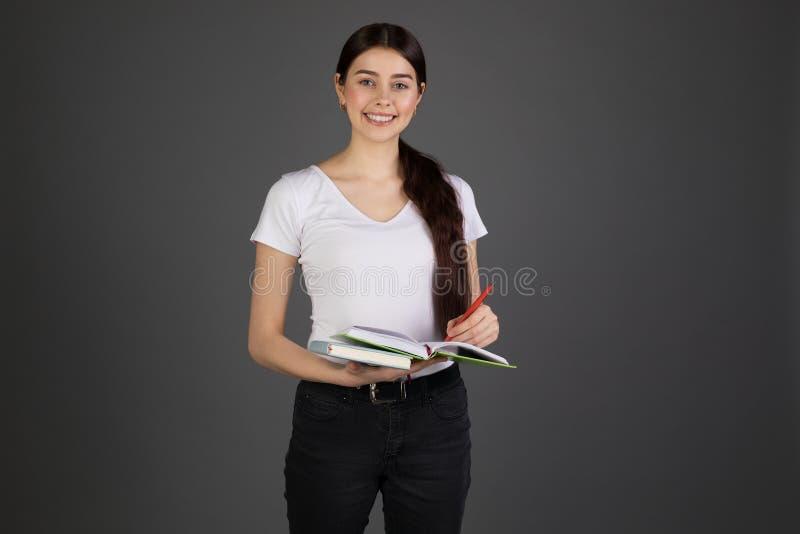 Retrato de encantar o estudante fêmea que escreve em seu caderno fotos de stock