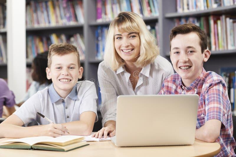Retrato de estudantes da High School de Helping Two Male do professor fêmea imagem de stock