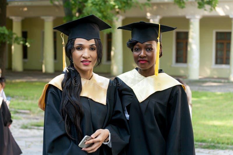 Retrato de estudantes felizes em vestidos da graduação imagem de stock royalty free