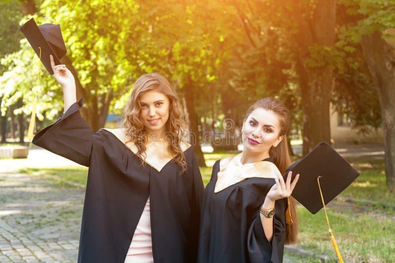 Retrato de estudiantes felices en vestidos de la graduación foto de archivo