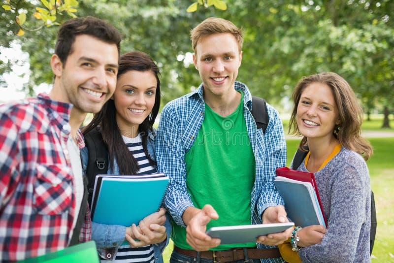 Retrato de estudiantes universitarios con los bolsos y de libros en parque foto de archivo libre de regalías