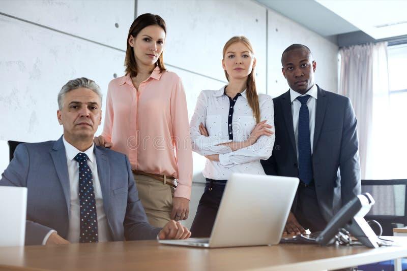 Retrato de executivos multi-étnicos seguros na mesa no escritório foto de stock royalty free
