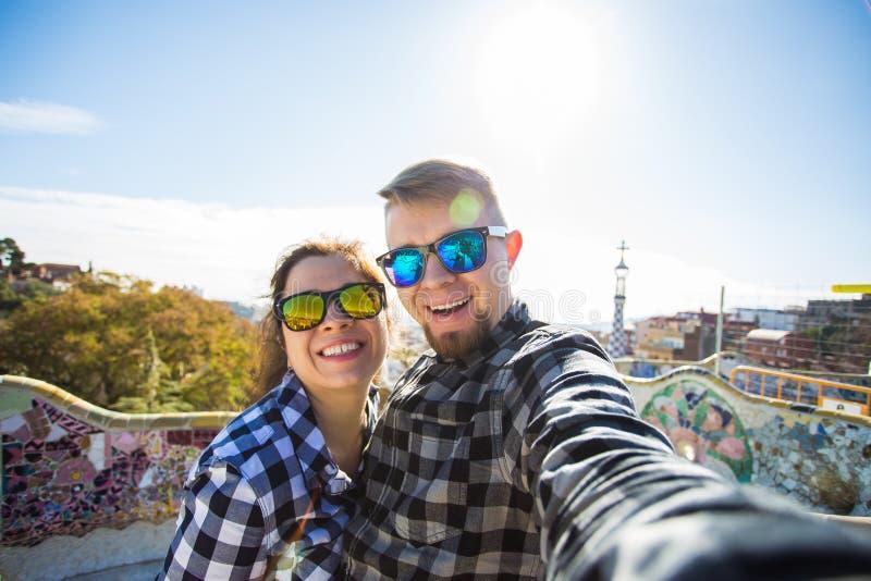 Retrato de fabricación feliz del selfie de los pares del viaje con smartphone en el parque Guell, Barcelona, España fotos de archivo libres de regalías