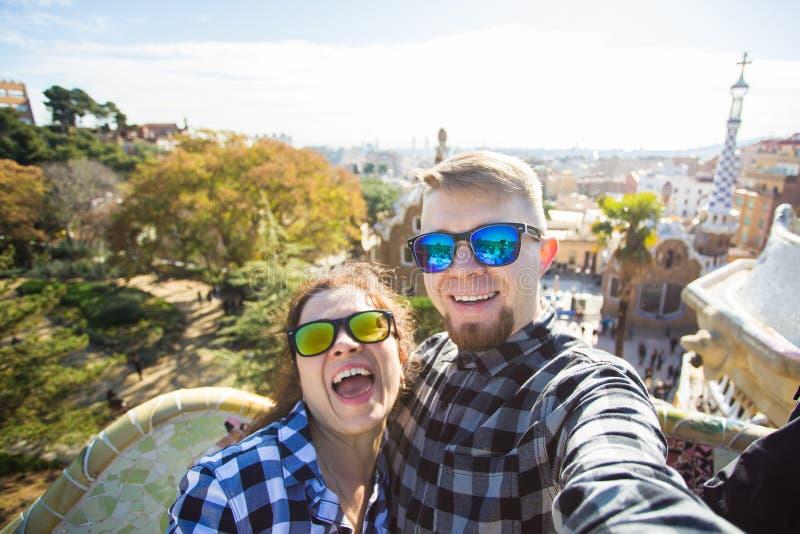 Retrato de fabricación feliz del selfie de los pares del viaje con smartphone en el parque Guell, Barcelona, España imagen de archivo libre de regalías