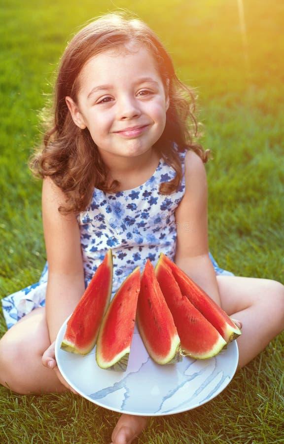 Retrato de fatias de sorriso da melancia da terra arrendada da menina no jardim fotografia de stock