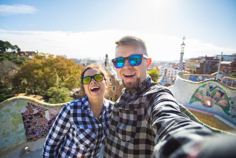Retrato de fatura feliz do selfie dos pares do curso com o smartphone no parque Guell, Barcelona, Espanha imagem de stock