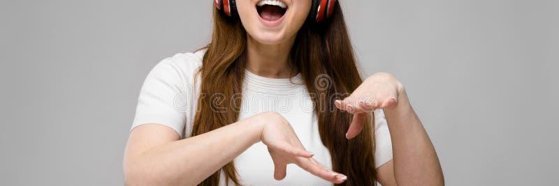 Retrato de feliz bonito emocional mais o modelo do tamanho nos fones de ouvido e nos óculos de sol que estão no estúdio que olha  imagem de stock