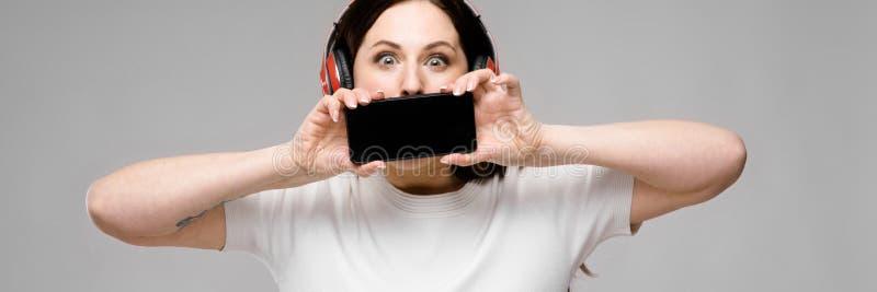 Retrato de feliz bonito emocional mais o modelo do tamanho nos fones de ouvido que guardam o telefone celular atrás de sua boca q fotos de stock royalty free