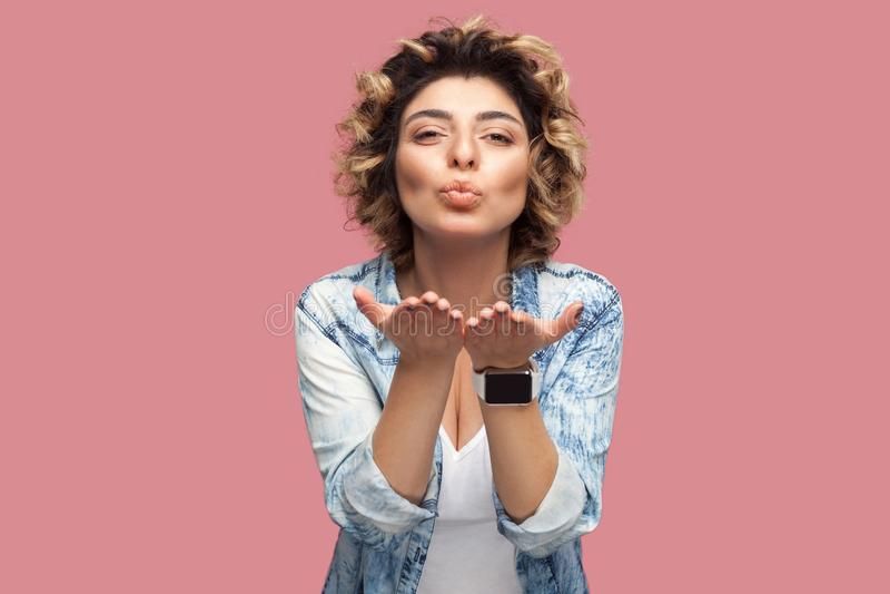 Retrato de feliz na jovem mulher do amor com penteado encaracolado na posição azul ocasional da camisa, olhando a câmera e envian imagens de stock