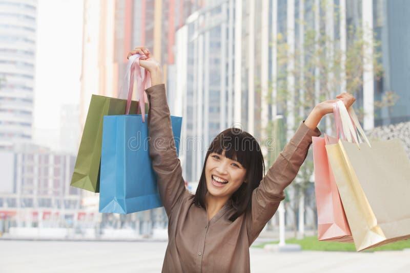 Retrato de feliz, sorrindo, jovem mulher que guardara sacos de compras coloridos no ar na rua no Pequim, China imagens de stock royalty free