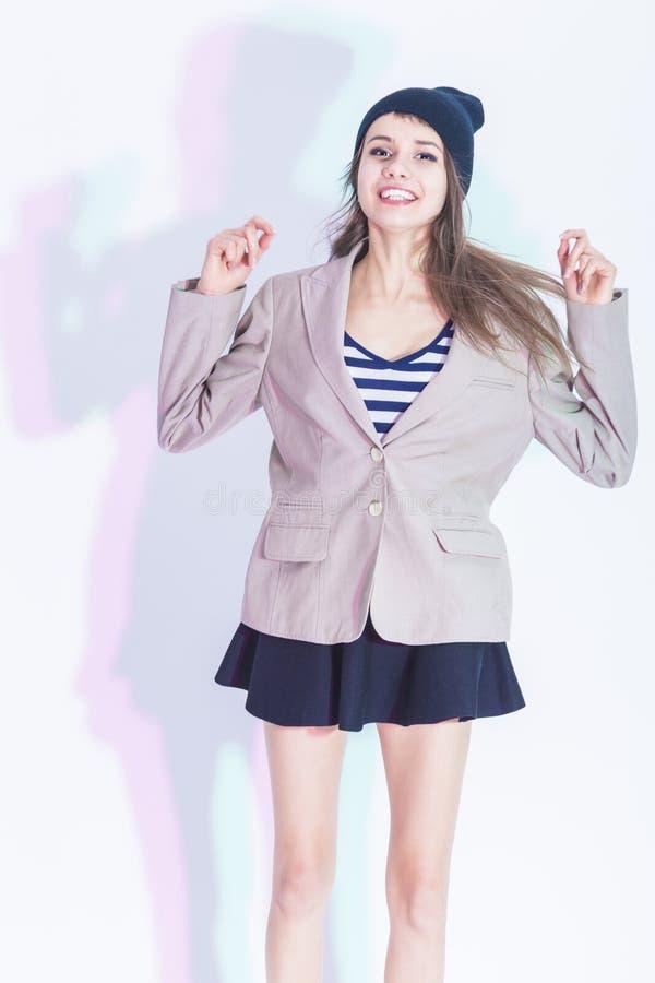 Retrato de feliz y Glad Exclaiming Thin Brunette Girl en la chaqueta de moda que presenta en falda atractiva imagenes de archivo