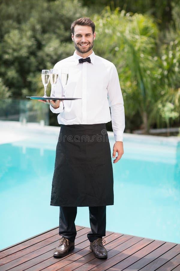 Retrato de flautas de champanhe levando de sorriso do garçom foto de stock royalty free