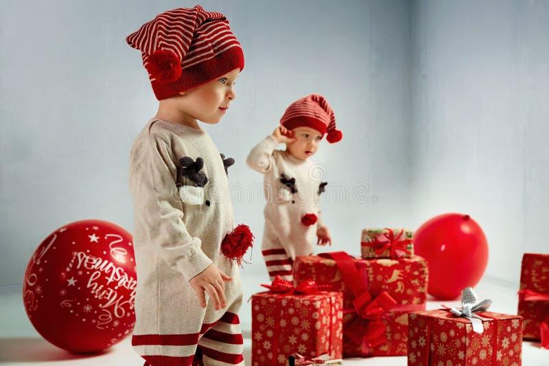 Retrato de gêmeo-duendes adroable entre presentes de Natal enormes fotografia de stock royalty free