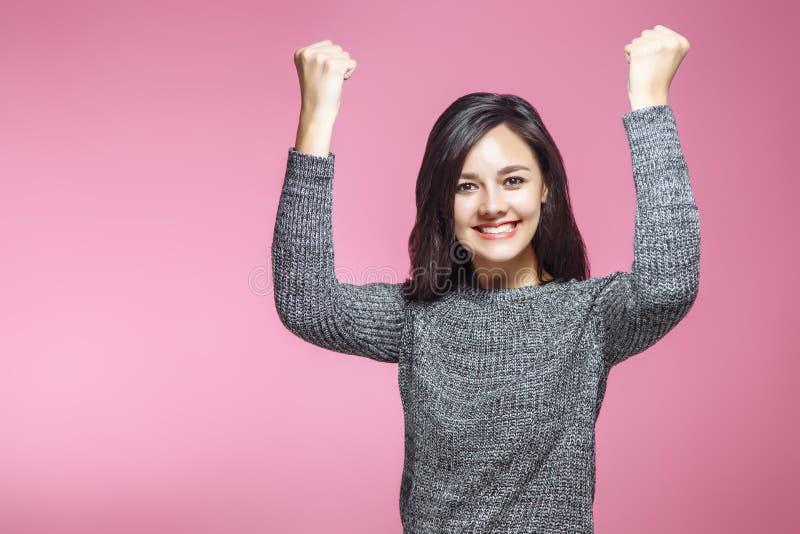 Retrato de ganar a la mujer de negocios joven acertada, celebración extática feliz siendo ganador, en fondo rosado Positiv imagen de archivo libre de regalías