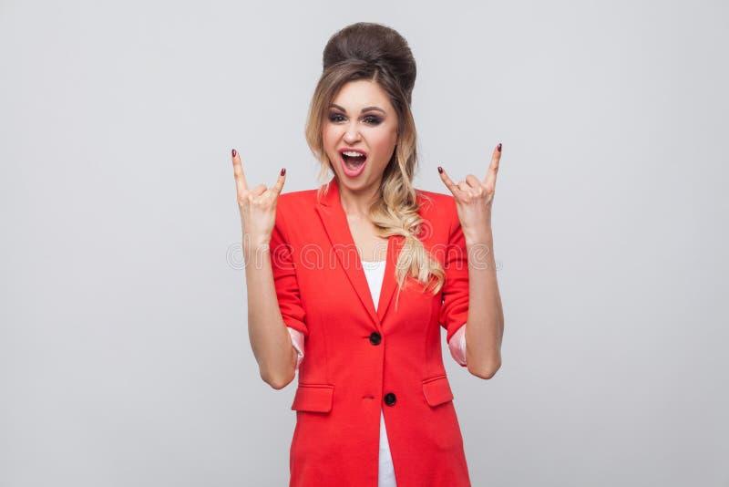 Retrato de gritar a la señora hermosa del negocio con el peinado y el maquillaje en chaqueta de lujo roja, colocándose con la mue fotografía de archivo