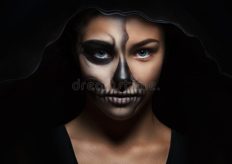 Retrato de Halloween de la muchacha hermosa joven en una capilla negra maquillaje esquelético foto de archivo libre de regalías