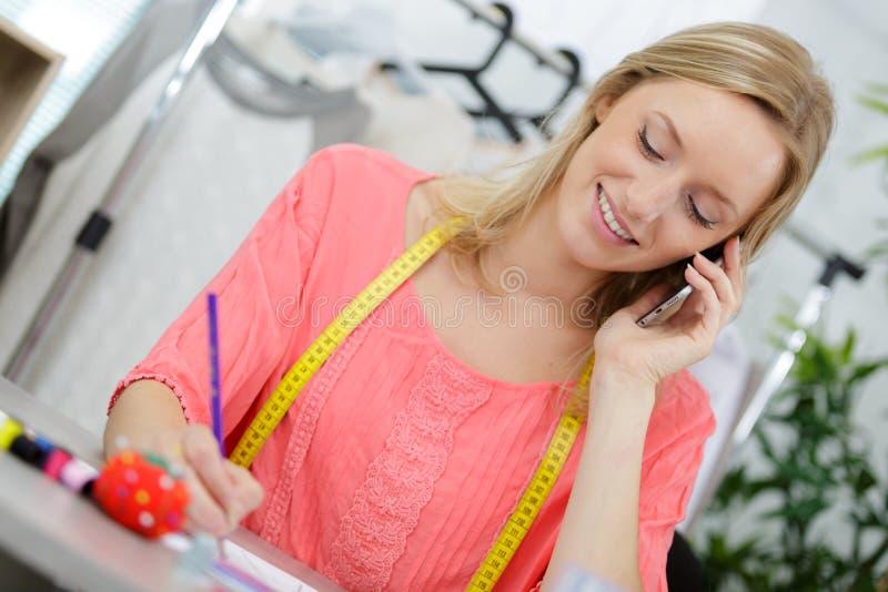 Retrato de hermosa costurera hablando por teléfono imagen de archivo libre de regalías