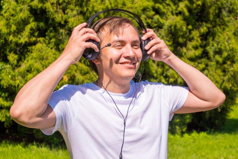 Retrato de hombres en auriculares, en la situaci?n blanca de la camiseta exterior en parque fotos de archivo