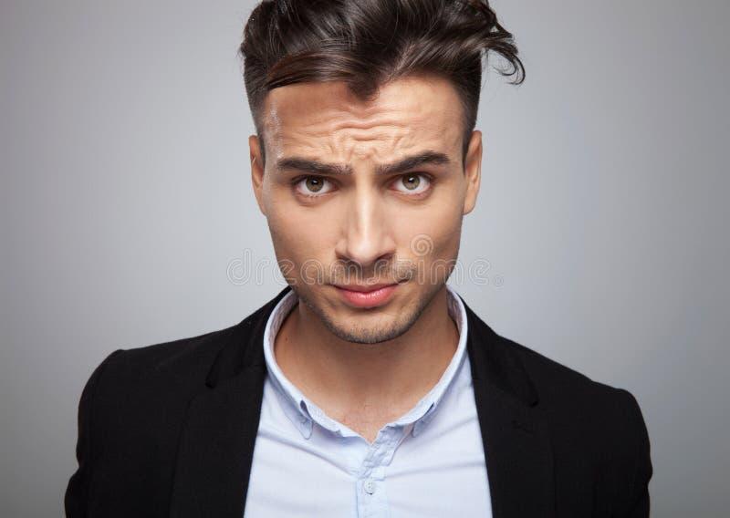 Retrato de homem de negócios frustrante na posição preta do terno fotografia de stock