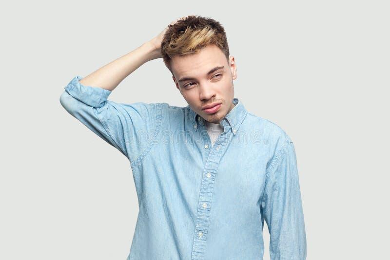 Retrato de homem novo consider?vel confuso em claro - posi??o azul da camisa, riscando sua cabe?a, olhando afastado e pensando qu imagem de stock