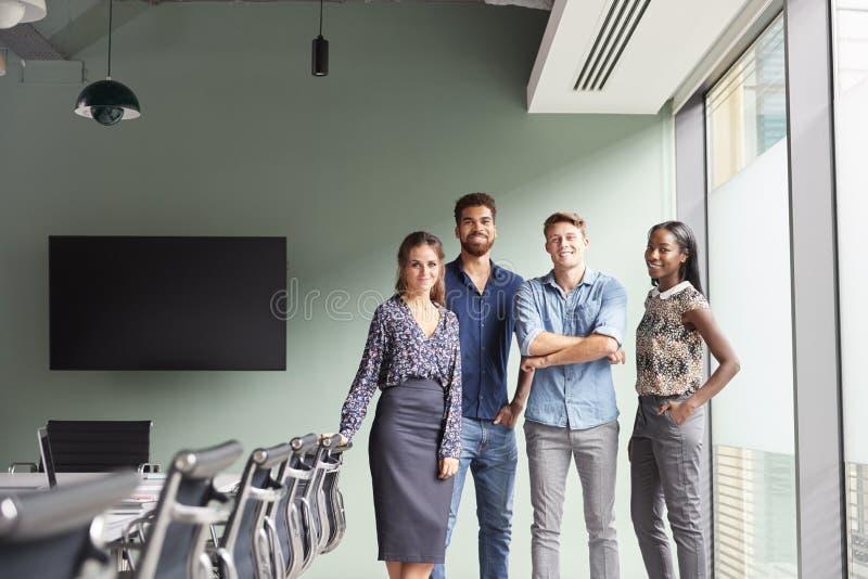 Retrato de homens de negócios ocasionalmente vestidos e de mulheres de negócios que têm a reunião informal na sala de reuniões mo imagens de stock royalty free