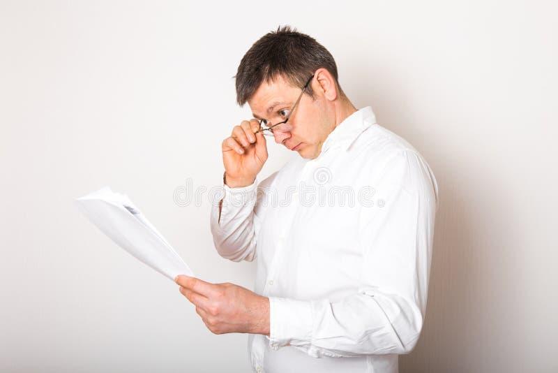 Retrato de humorístico hombre de negocios caucásico sorprendido con lentes abiertos para ver reportes financieros, concepto de ma fotos de archivo