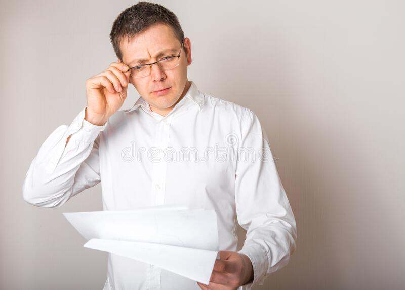 Retrato de humorístico hombre de negocios caucásico sorprendido con lentes abiertos para ver reportes financieros, concepto de ma fotografía de archivo