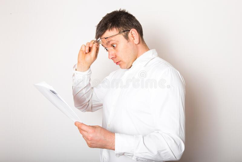 Retrato de humorístico hombre de negocios caucásico sorprendido con lentes abiertos para ver reportes financieros, concepto de ma imagenes de archivo