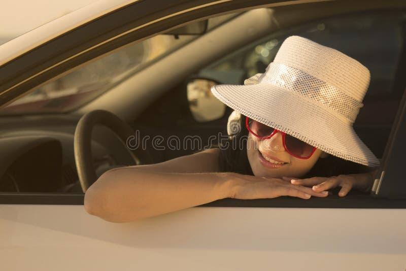 Retrato de inclinarse femenino joven en la ventanilla del coche imagen de archivo