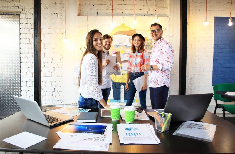 Retrato de jovens felizes em uma reunião que olha a câmera e o sorriso Desenhistas novos que trabalham junto na imagem de stock