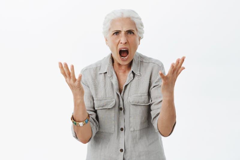 Retrato de la abuela furiosa y enojada descontenta con el pelo blanco en la camisa sport que aumenta las palmas en gesto desorien foto de archivo libre de regalías