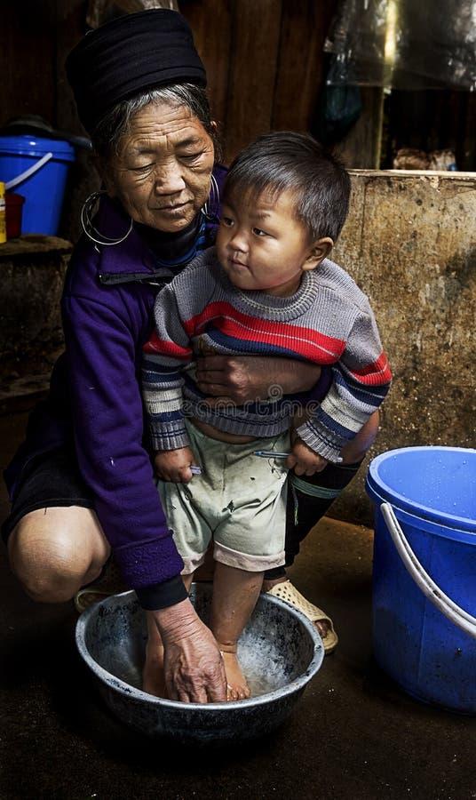 Retrato de la abuela de la tribu de Hmong y de su nieto en su casa tradicional en Sapa, Vietnam imagenes de archivo