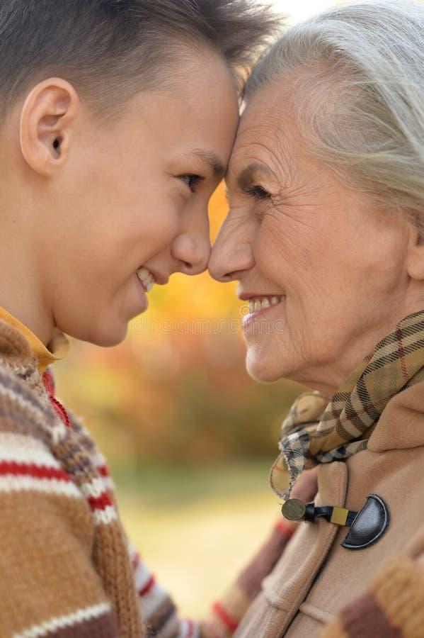 Retrato de la abuela y del nieto que abrazan en parque foto de archivo