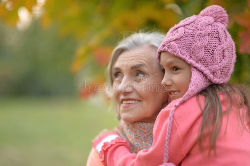 Retrato de la abuela y de la nieta en parque otoñal foto de archivo